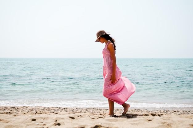 mujer-mirando-la-arena-de-la-playa-mientras-camina_1139-340